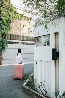 Ragazza a piedi con i bagagli rosa