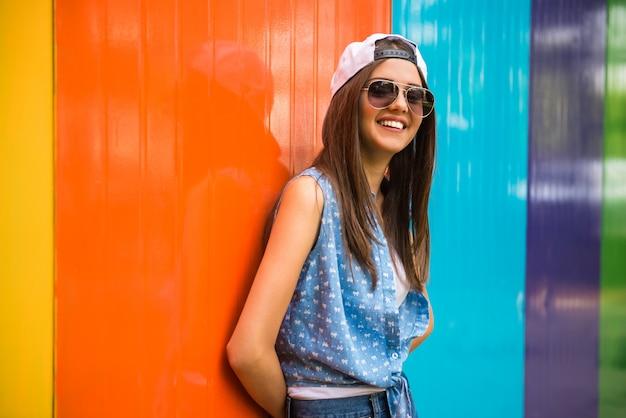 Ragazza abbastanza alla moda in occhiali da sole e berretto.