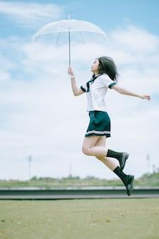 Ragazza abbastanza asiatica allegra in uniforme dello studente giapponese che tiene un ombrello trasparente mentre saltando per la gioia in un campo aperto un bello giorno del cielo blu