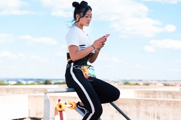 Ragazza abbastanza asiatica con il telefono cellulare, abbigliamento casual, in un parco