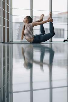 Ragazza abbastanza attraente che fa yoga e che si distende nella stanza luminosa