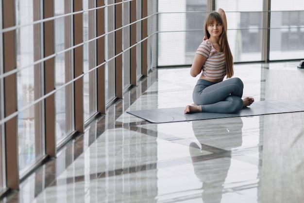 Ragazza abbastanza attraente che fa yoga in una stanza luminosa