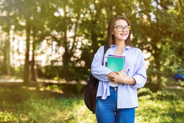 Ragazza abbastanza attraente con i libri in piedi e sorridente nel parco