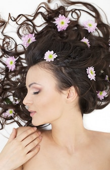 Ragazza abbastanza bella che si trova con i fiori luminosi nel suo trucco luminoso dei capelli isolato su bianco