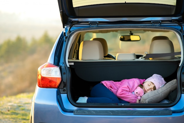 Ragazza abbastanza felice del bambino che dorme con un orsacchiotto rosa del giocattolo in un tronco di automobile.
