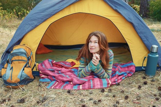 Ragazza abbastanza giovane di redhead che osserva in su, trovandosi in tenda grigia gialla, distendendosi, godendo della natura nella foresta di autunno. escursionismo, viaggi, meditazione, concetto di turismo verde. stile di vita attivo sano