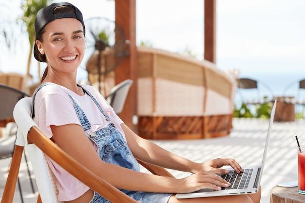 Ragazza abbastanza giovane hipster con un sorriso piacevole, ha un aspetto positivo, vestito casualyy, riposa in un caffè all'aperto, naviga nei social network sul computer portatile portatile