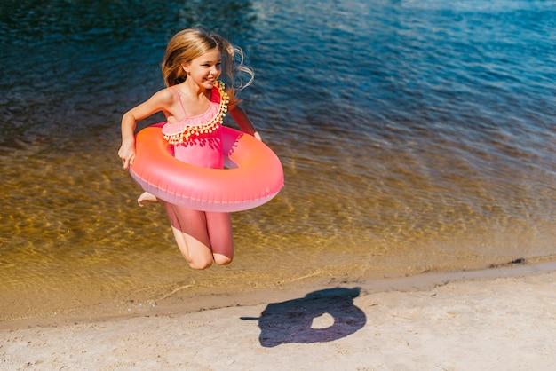 Ragazza abbastanza spensierata in costume da bagno saltando in riva al mare