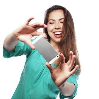 Ragazza abbastanza teenager che prende i selfie