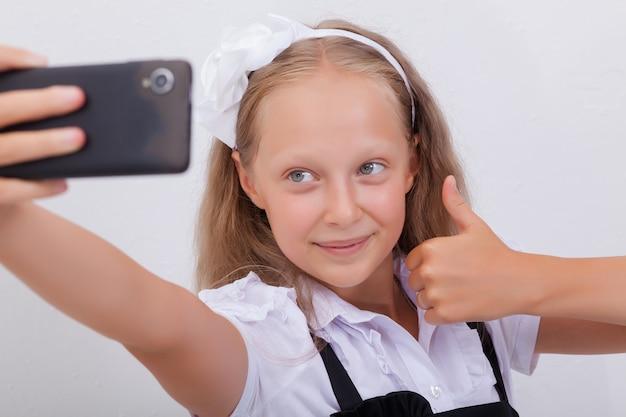 Ragazza abbastanza teenager che prende i selfies con il suo smartphone