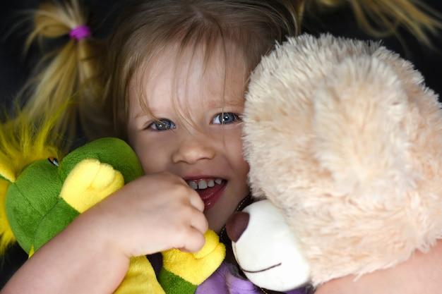 Ragazza abbraccia giocattoli di peluche e ride