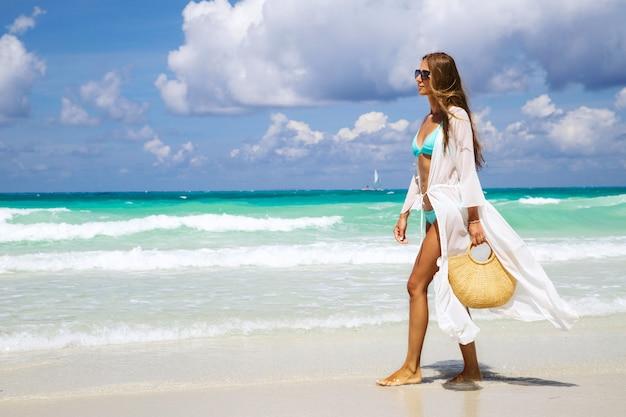 Ragazza abbronzata in bikini blu e tunica bianca che tiene la borsa di paglia alla moda e camminare in riva al mare.