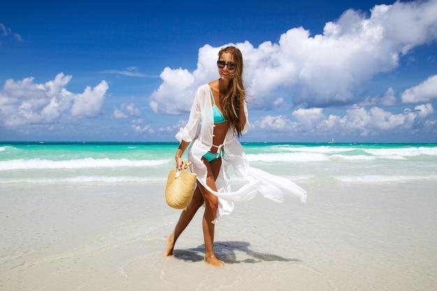 Ragazza abbronzata in bikini blu e tunica bianca in piedi in riva al mare.