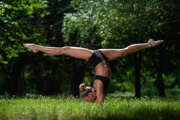 Ragazza-acrobata sportiva in piedi sulle sue mani, eseguendo spago