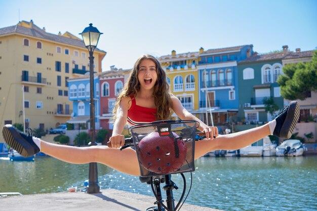 Ragazza acrobatica in sella a una bicicletta in un porto turistico