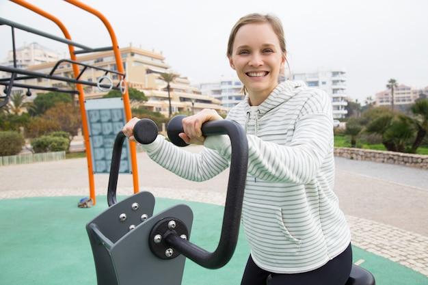 Ragazza adatta allegra che risolve sulla bici di esercizio