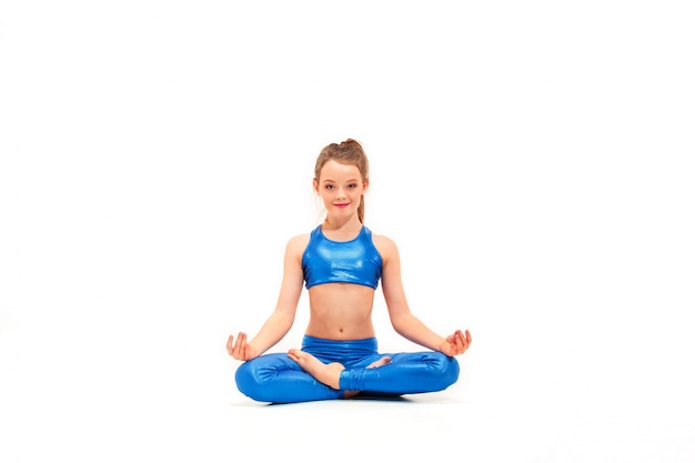 Ragazza adatta dei giovani che fa le esercitazioni di yoga su bianco