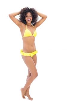Ragazza adatta in bikini giallo che sorride alla macchina fotografica