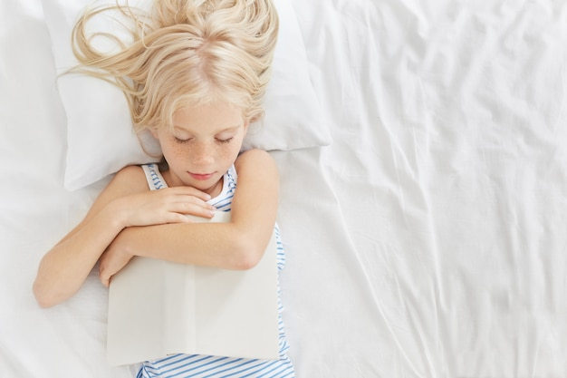 Ragazza addormentata con lunghi capelli biondi, tenere il libro in mano, addormentarsi dopo aver letto fantasia o fiabe, avere sogni piacevoli. bambino che riposa in una stanza confortevole dopo il gioco attivo con gli amici