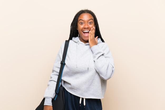 Ragazza adolescente afroamericana sportiva con capelli lunghi intrecciati con espressione facciale sorpresa e scioccata
