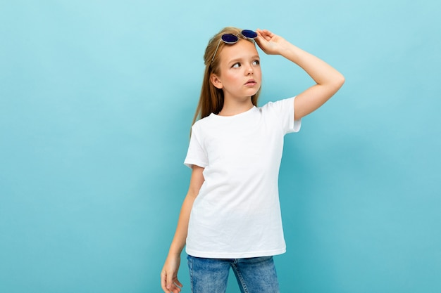 Ragazza adolescente caucasica con i capelli castani in giacca nera detiene occhiali da sole isolati su blu