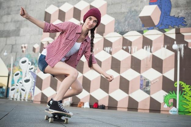 Ragazza adolescente divertendosi la sera d'estate all'aperto. lei fa skateboard