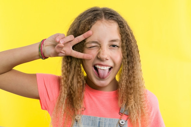 Ragazza adolescente gesticolando, mostrando la lingua, coprendo un occhio