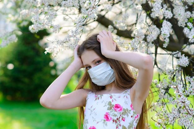 Ragazza adolescente in maschera medica protettiva in primavera tra il giardino fiorito.