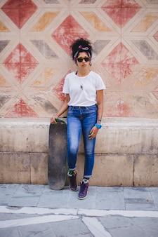 Ragazza adolescente in possesso di skateboard in piedi