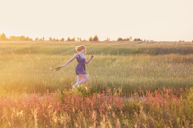 Ragazza adolescente nel campo estivo al tramonto