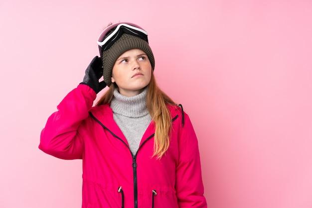 Ragazza adolescente sciatore con occhiali da snowboard con dubbi e con espressione del viso confuso