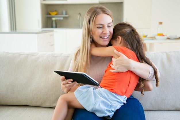 Ragazza adorabile che abbraccia la sua mamma che ride mentre utilizza tablet.