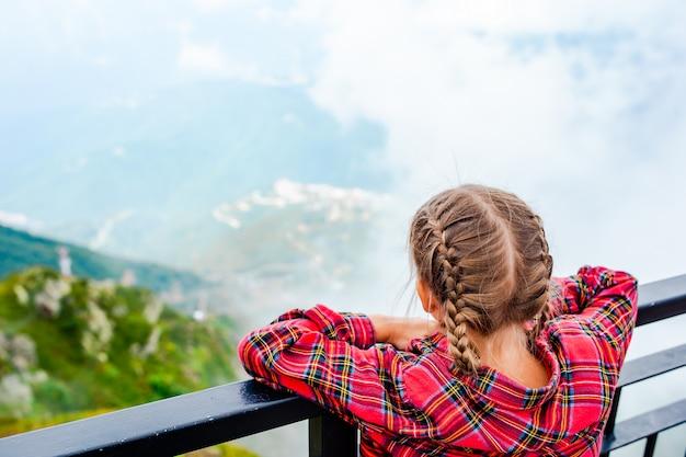 Ragazza adorabile che esamina le montagne
