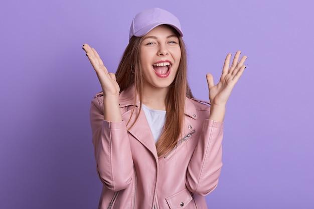 Ragazza adorabile che grida felicemente mentre posa coperta contro la parete lilla con le palme su