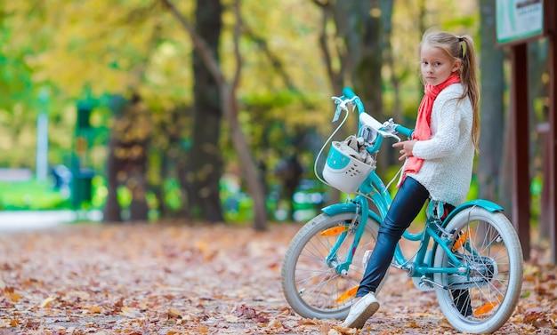 Ragazza adorabile che guida una bici al bello giorno di autunno all'aperto