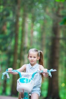 Ragazza adorabile che guida una bici al bello giorno di estate all'aperto