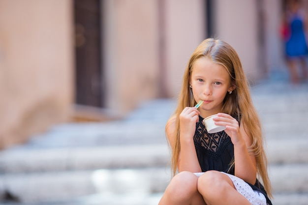 Ragazza adorabile che mangia gelato all'aperto all'estate nella città