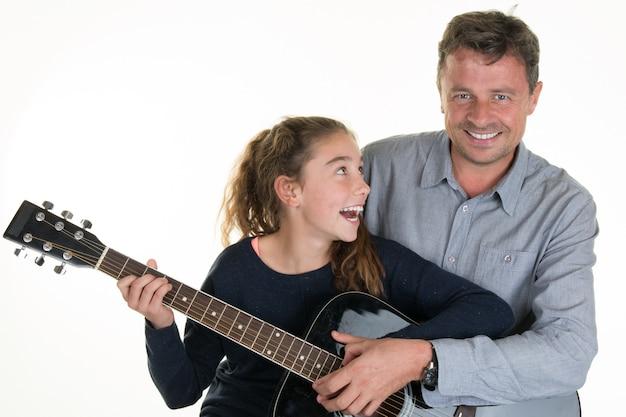 Ragazza adorabile che ottiene le lezioni di chitarra con l'uomo