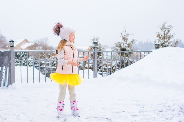 Ragazza adorabile che pattina sulla pista di pattinaggio sul ghiaccio all'aperto nel giorno della neve di inverno