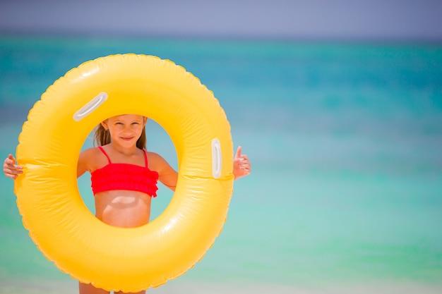 Ragazza adorabile con il cerchio di gomma gonfiabile sulla spiaggia bianca