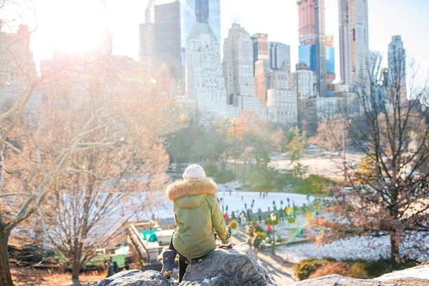 Ragazza adorabile con la vista della pista di pattinaggio sul ghiaccio in central park su manhattan a new york city