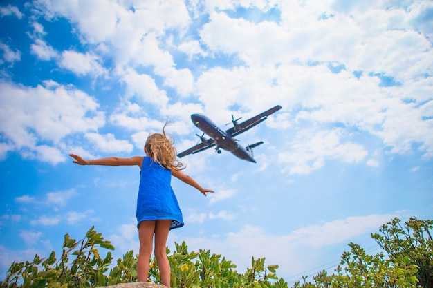 Ragazza adorabile del piccolo bambino che guarda al cielo e aereo di volo direttamente sopra lei. bella immagine emozionante