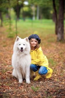 Ragazza adorabile in stivali di gomma gialli e cappotto di pioggia sulle passeggiate, gioca con un bellissimo cane samoiedo bianco nel parco in autunno