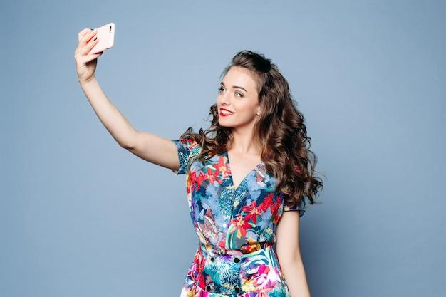 Ragazza adorabile in vestito floreale che prende selfie con il telefono cellulare più