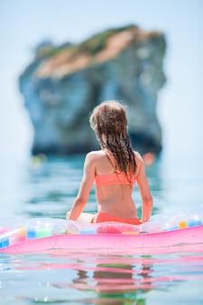 Ragazza adorabile sul materasso di aria gonfiabile nel mare