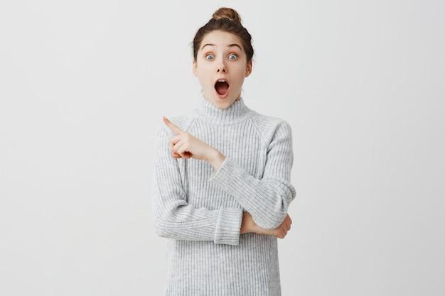 Ragazza adulta che sta con la bocca aperta e che mostra il dito indice a qualcosa di eccitante. emozioni divertenti dell'adolescente femminile che sono colpite e felici. concetto di divertimento
