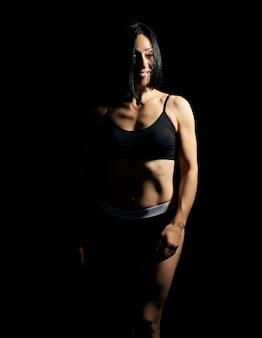 Ragazza adulta con una figura sportiva in reggiseno nero e pantaloncini neri