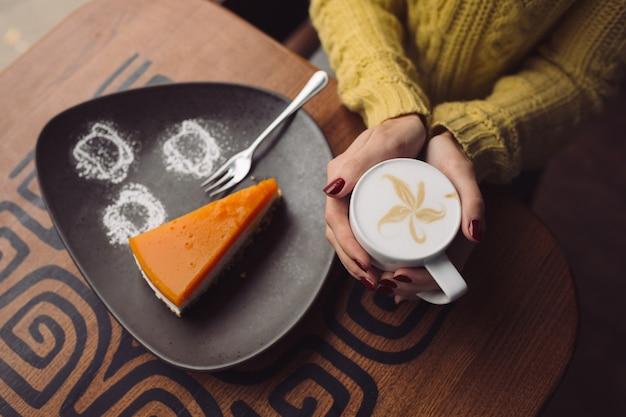 Ragazza affascinante che beve cappuccino e cheesecake di cibo