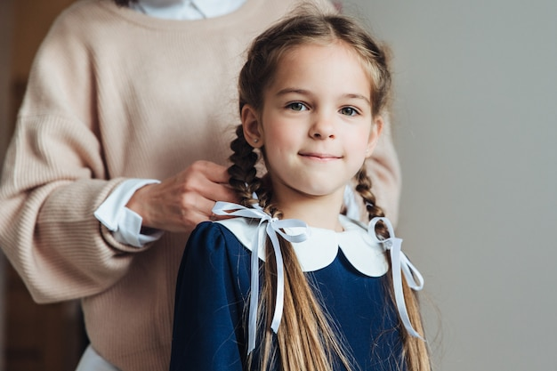 Ragazza affascinante con la madre che fissa i suoi capelli