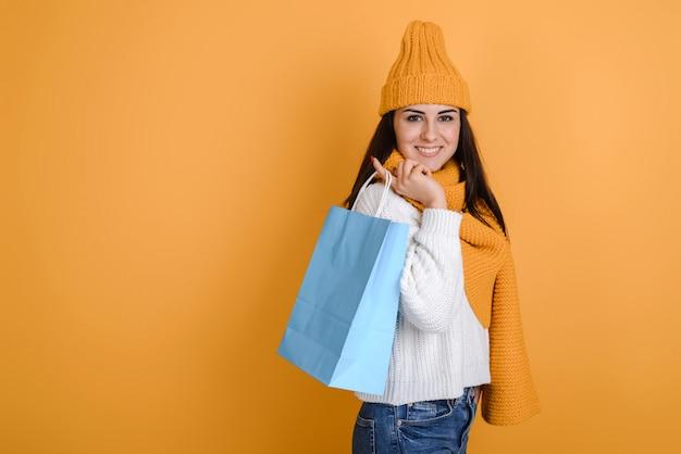 Ragazza affascinante in cappello e sciarpa tricottati con i sacchetti della spesa che posano nello studio